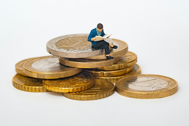 Small figured man sitting on a pile of coins.